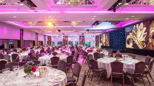 Royal Lancaster London ballroom, decked round tables with a pink light ceiling.