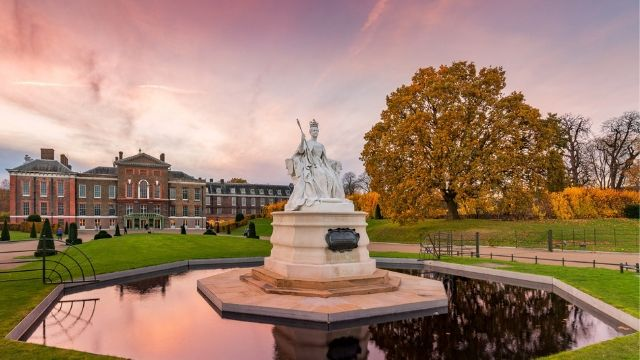Fountain with a white statue in the middle in Kensington Palace gardens, with a rosy sunset sky in the background, reflecting in the water.