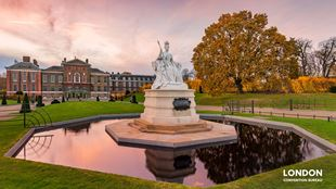 Kensington Palace at sunset, the pink clouds are reflecting in the water of a big fountain.