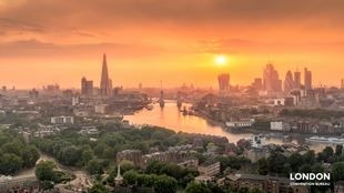 The London skyline and river Thames covered in orange light during sunset.