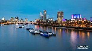 The riverside in the evening with purple and yellow lights of the buildings reflecting in the Thames.
