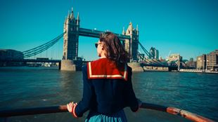 Woman on Thames boat ride in front of Tower Bridge