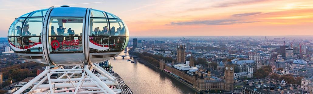 View over the Houses of Parliament, Westminster and beyond from a London Eye pod filled with visitors.