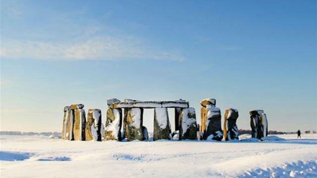 Stonehenge site covered in snow with blue sky in the background.