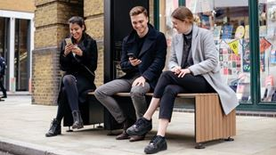 Three people sat on a bench outside a bookshop, looking at their phones and smiling.