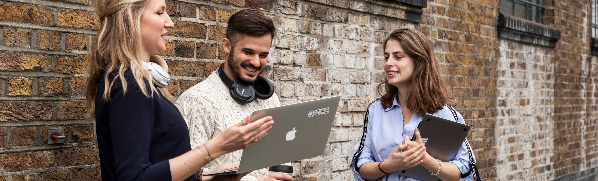 Two young people are standing in front of a brick wall, holding a large iPad and notebook, having a work catch up.