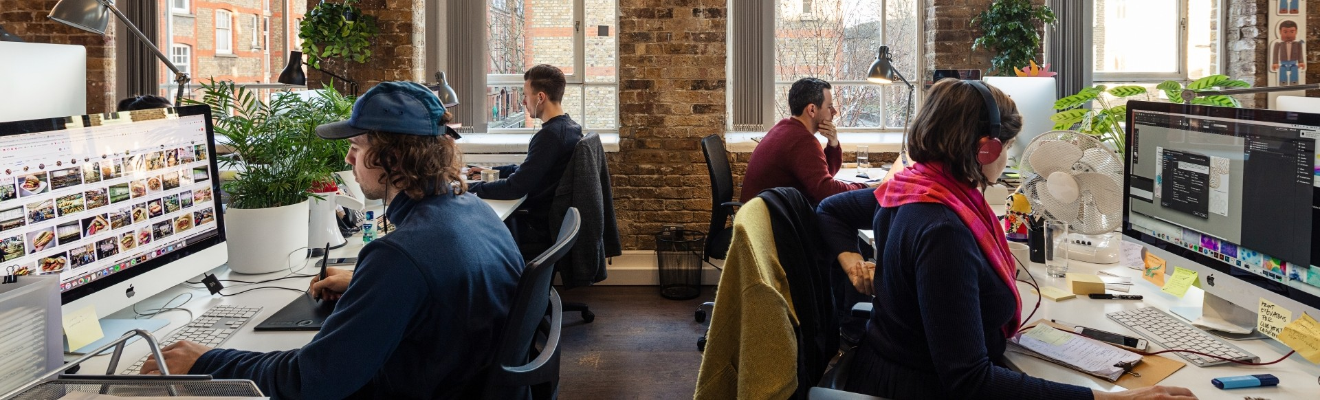 Four employees working in a trendy brick office with plants and iMac computers.