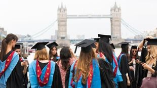 A group of students of the Istituto Marangoni during their graduation ceremony are wearing long black robes and square hats with Tower Bridge in the background.