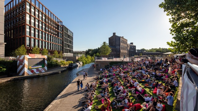 A large crowd is sitting on steps by the canal in King's Cross on a beautiful sunny day, watching a film on a giant screen positioned on the other side.
