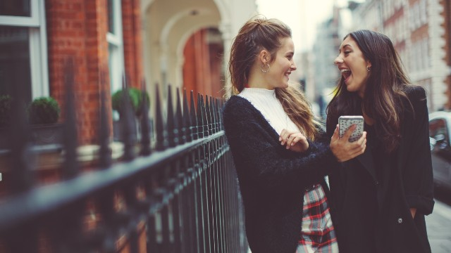 Two young students on the street are looking at each other with bright smiles after checking their phone together.