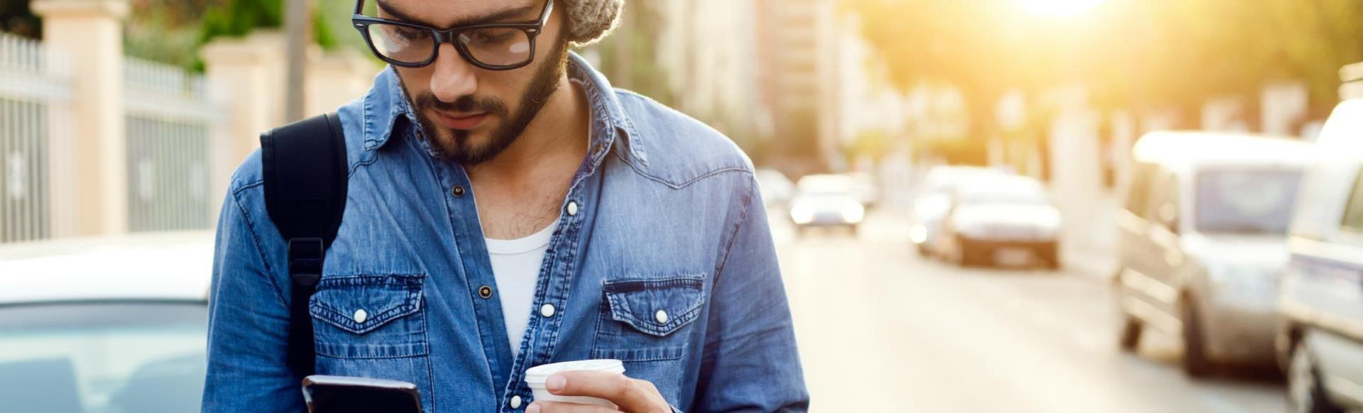 Молодой бородатый мужчина идет по улице, смотрит в свой телефон, а за его спиной встает солнце.