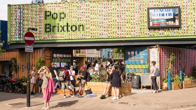 People stand in the sunshine outside container village Pop Brixton