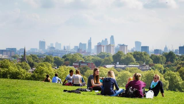 People enjoy the sunshine on Primrose Hill in London with the city of London in the distance