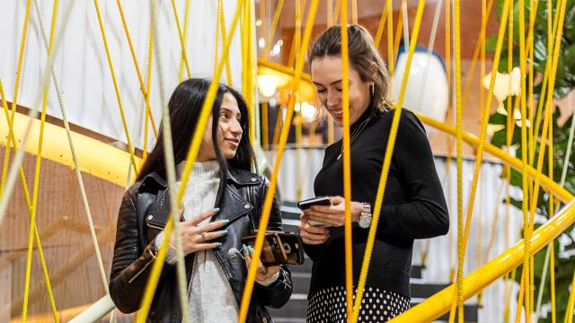 Two people share a joke on a staircase wrapped with yellow steel rods at Second Home in Spitalfields