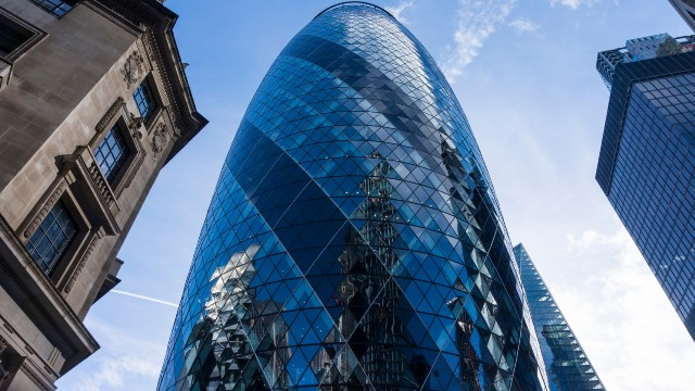 The Gherkin viewed from the streets on a sunny day in London.
