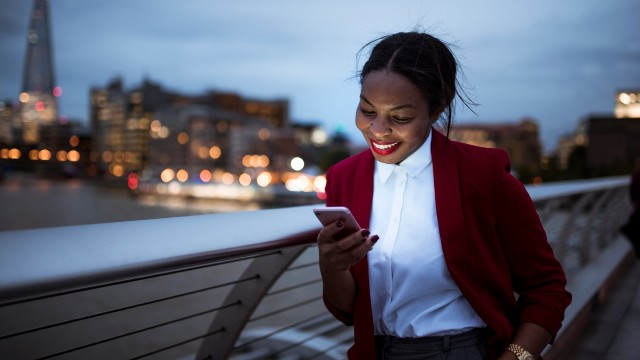 A young professional woman with a white shirt and red jacket is looking down at her lit phone by the river Thames as the sun sets.