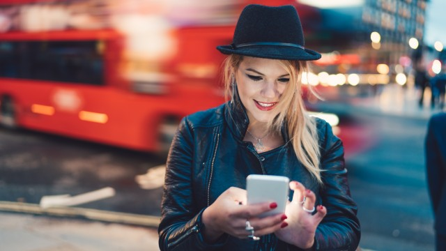 A young woman wearing a black leather jacket and hat is looking down at her phone as a red double deck bus blurs in the background.