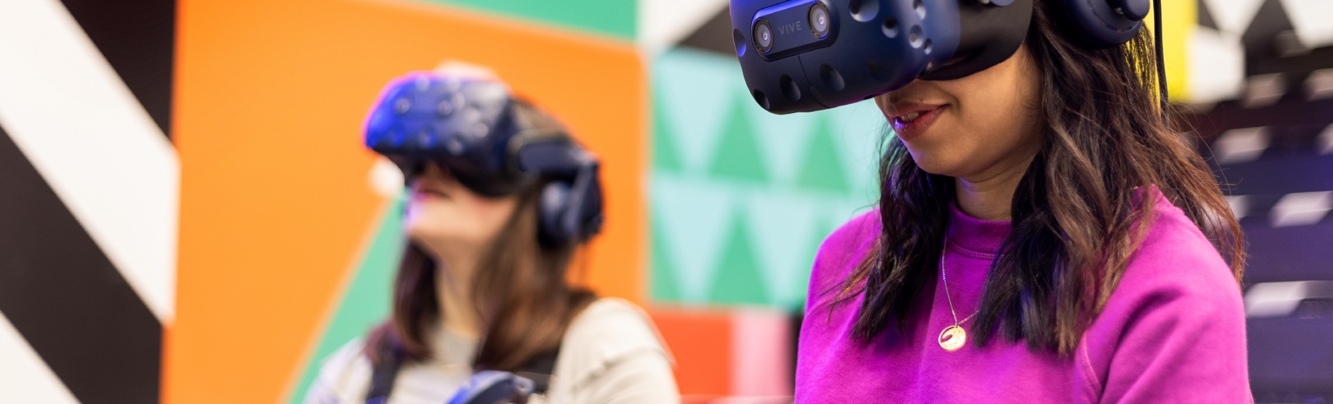 Two young woman are wearing black virtual reality headset, dressed in colourful outfits.