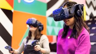Two young women are wearing black virtual reality headset, dressed in colourful outfits.