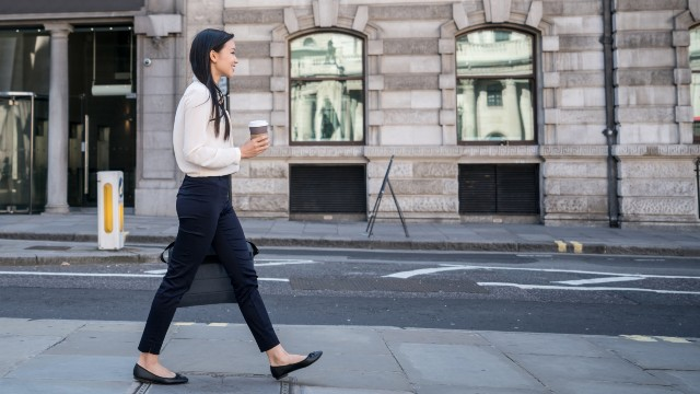 A woman dressed in office clothes is on her way to work in London.