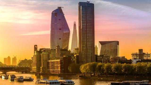 The sun sets in London, displaying beautiful orange skies behind skyscrapers in London.