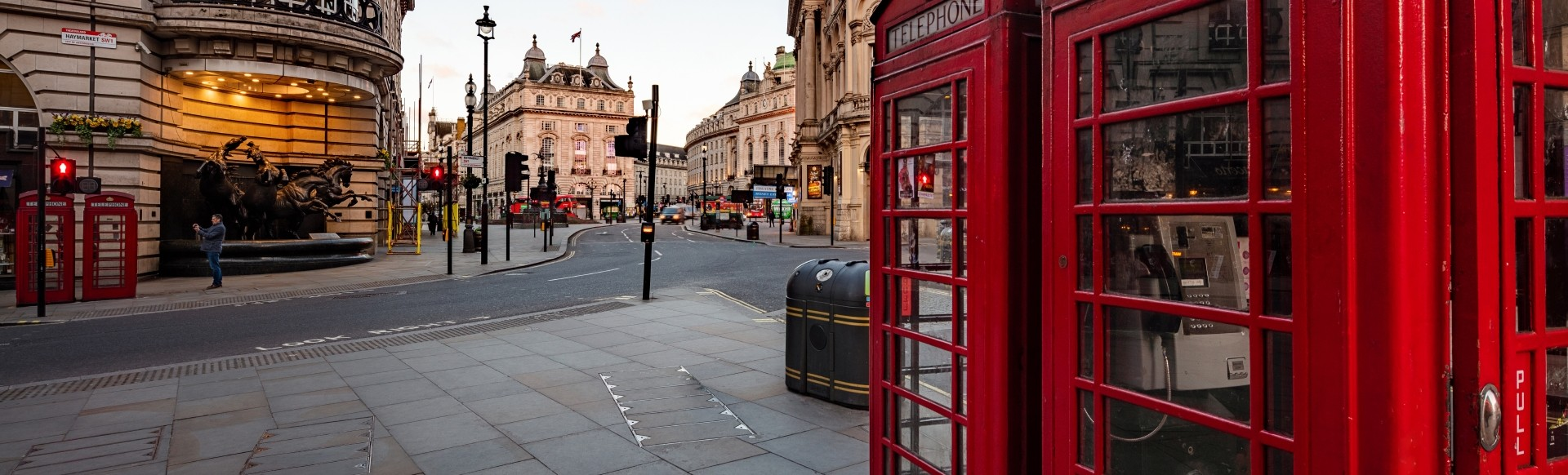 Two red London telephone booths by an empty Piccadilly Circus at sunrise.