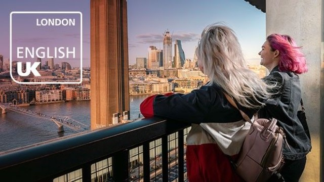 Two young women are standing on a outdoor terrace, facing London's skyline on a sunny day.