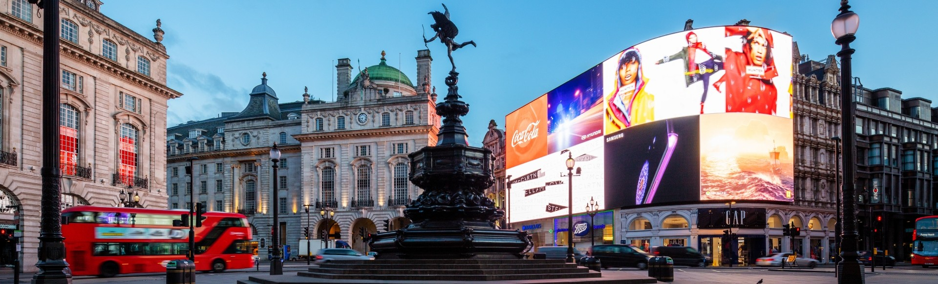 Panoramic view of a large bright advertising board with advertising, a double deck red bus and a black varnished fountain in the centre.