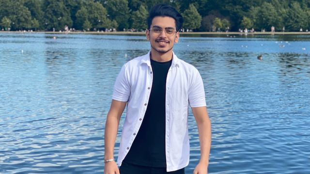 A young man is smiling and standing in front of a lake.