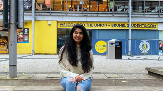 A young lady is sitting on steps outside of Brunel University London.