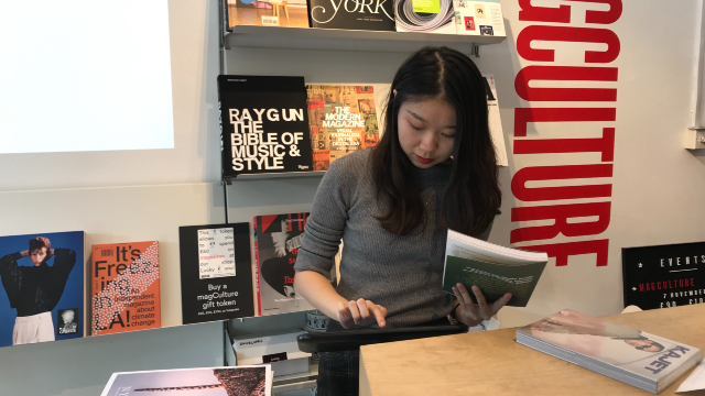Yan Li is standing by a till, typing on the screen and holding a book in her hand.