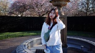 A young woman wearing a white hoodie is standing in front of a fountain and cherry blossomed trees on a sunny day.