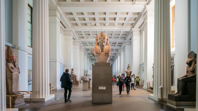 The Egyptian Sculpture Gallery at the British Museum, showing sculptures left, right and centre in a pale-blue room with white columns and roof