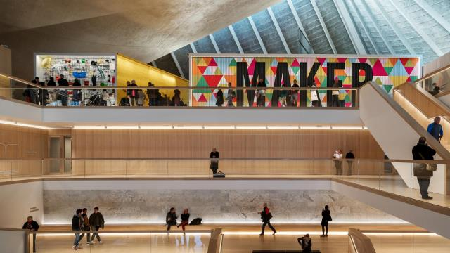 The interior of the Design Museum in London showing the multi-level atrium, staircase up to the large, brightly coloured Maker mural and the angular ceiling in the background