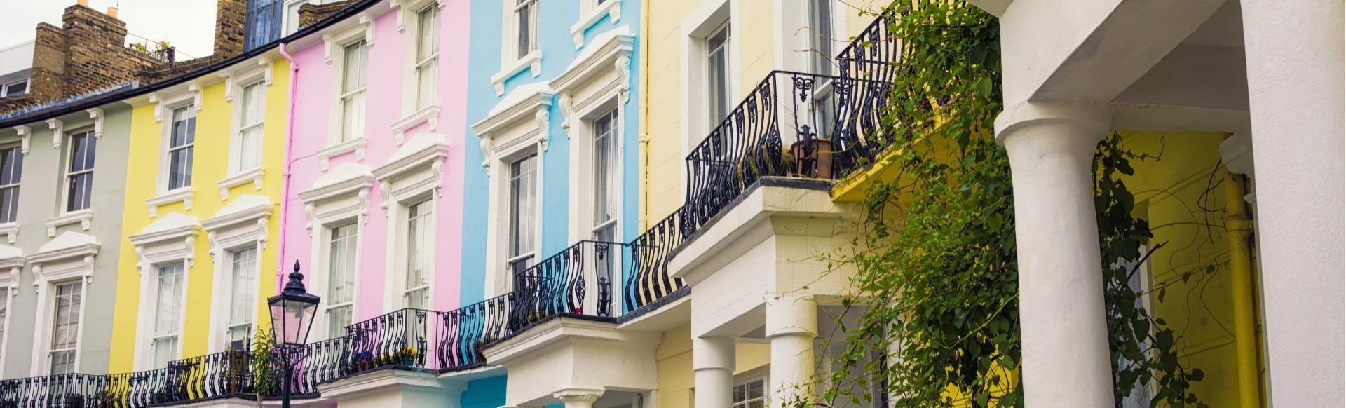 A row of colourful houses with columns at the entrance in Notting Hill.