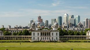 View from a hill of the Naval College in Greenwich and the Canary Wharf skyline in the background.