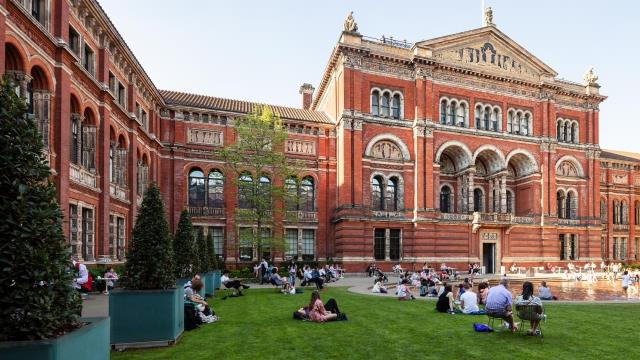 People relax on the grass in the courtyard at the Victoria and Albert museum