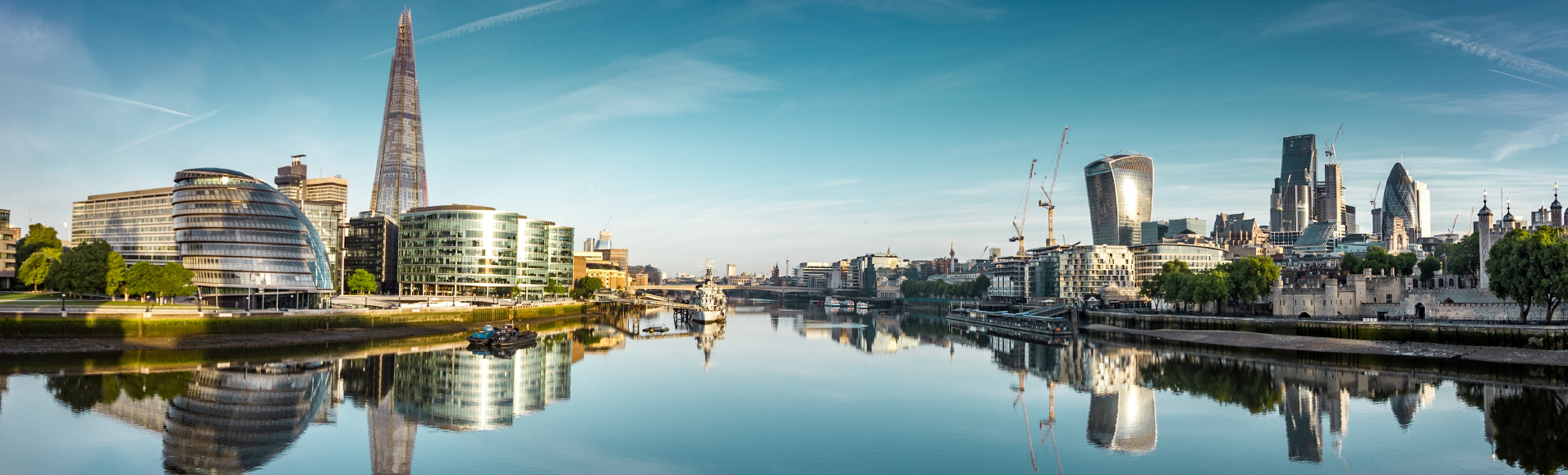 A panoramic view of London Bridge, City Hall, HMS Belfast and the City from the river, on a very sunny day in London.