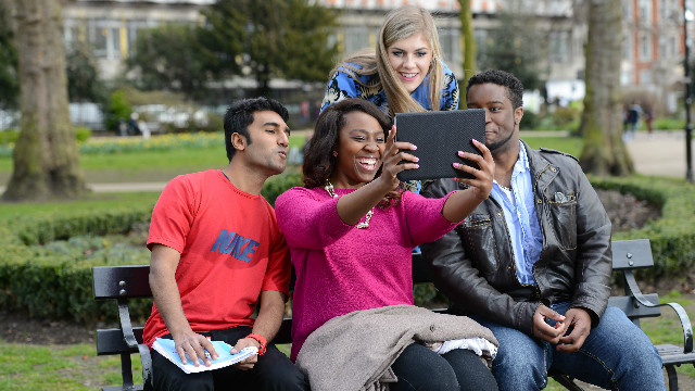 Four students sitting on a bench in a parc are taking a selfie with an Ipad.