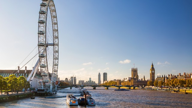 The sun shining over the river Thames, Westminster's Abbey and the London Eye.