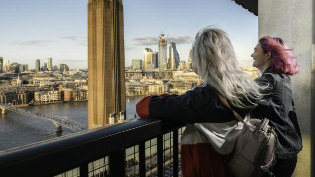 Two young women looking at river views from the top of Tate Modern's tenth floor in London.