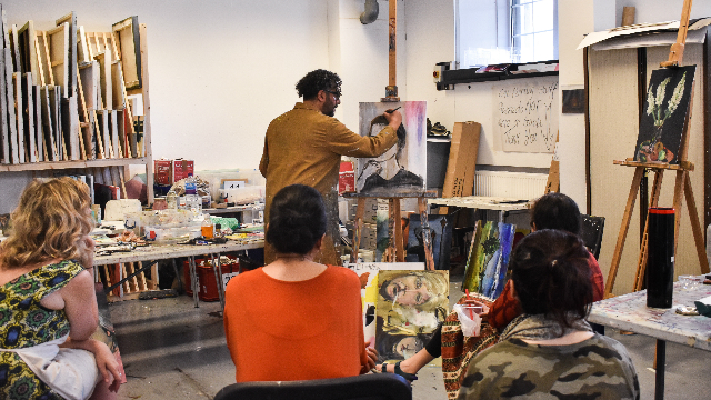 A teacher demonstrating to four students the art of portrait making in an art classroom.