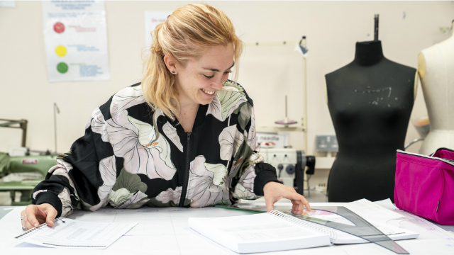 A smiling young woman, weraing a flowery bomber jacked is sitting at a desk and holding a set square while studying fashion.