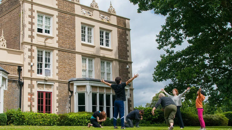 Four students dancing on the grass outside Rose Bruford College in London.