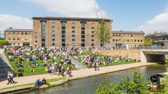 People sitting down in the sun and on the steps outside the University of the Arts' building, by the canal.