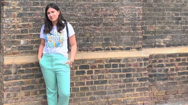 Ornella is standing by a wall, wearing turquoise trouser and a white teeshirt.