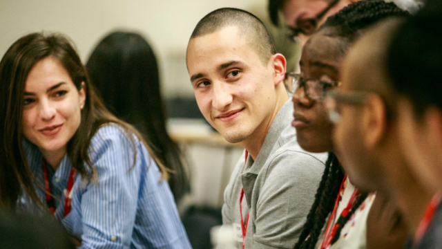 Victor who is a student at from Imperial College is smiling, surrounded by fellow students.