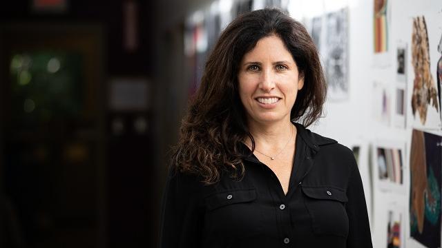 Julie has long brown wavy hair and is wearing a black long-sleeved teeshirt.
