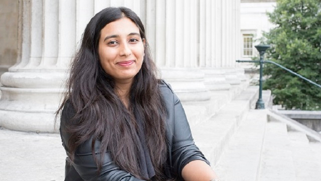 Portrait of Sonya, sitting on UCL's main entrance steps, outdoors.