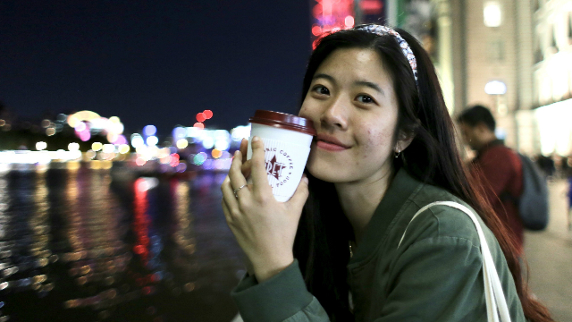 Student Danni is smiling and photographed at night time by the river Thames, holding a take away cup for a hot drink.